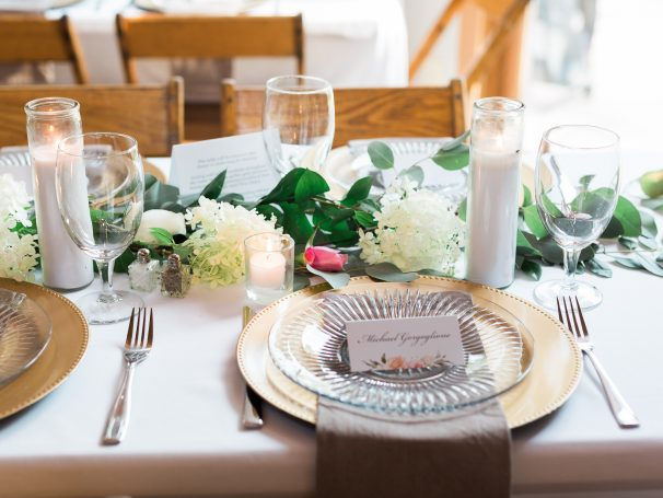 Gold Chargers | Poured Candles | White Table Linens | Natural Linen Napkins | Greenery & Floral Centerpieces | Gold Flatware