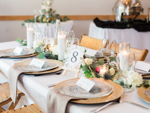 Gold Chargers | Poured Candles | White Table Linens | Natural Linen Napkins | Greenery & Floral Centerpieces | Gold Flatware | Custom Table Numbers
